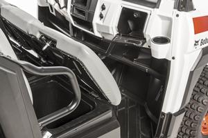Seats opened on Bobcat 3400 utility vehicle to show storage compartments.