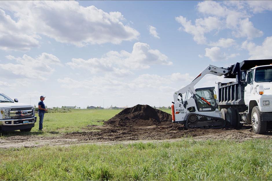 Bobcat operator uses the Bobcat MaxControl to dump dirt into a truck