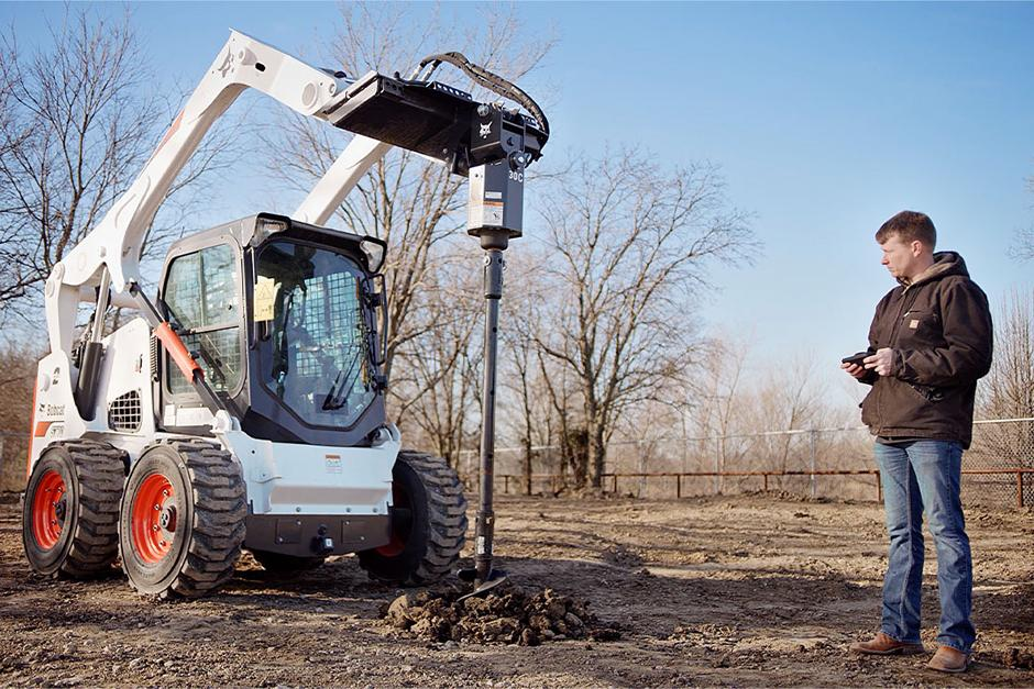 Bobcat operator uses the Bobcat MaxControl to dig holes for posts