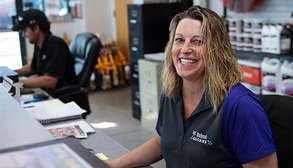 Female Bobcat Dealer Servicing Customers At A Desk