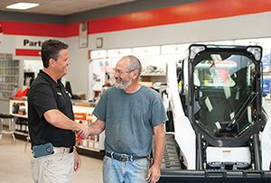 Bobcat dealer shaking hands with a customer in dealership