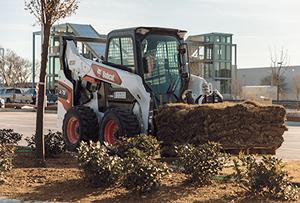 The new Bobcat R-Series Skid-Steer Loader with pallet attachment moving sod