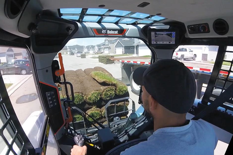 Operator Looks Out Through The Large Front Window Of The R-Series Loader As He Moves A Load Of Sod Around A Crowded Residential Worksite