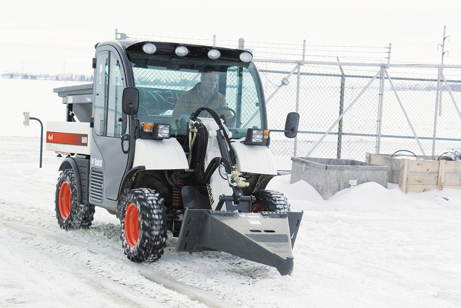 Operator Clears Parking Lot Of Ice With Scraper Attachment On Toolcat Work Machine