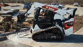 Operator Using Bobcat T76 Skid-Steer Loader With Tracks With Breaker Attachment To Break Through Concrete
