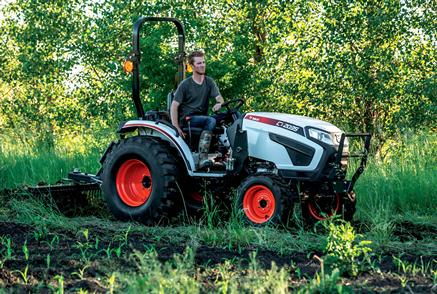 Bobcat Compact Tractor With Front-End Loader Driving on a Farm