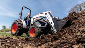 Acreage Owner Transports Dirt Using Front-End Loader Attachment On Bobcat Compact Tractor