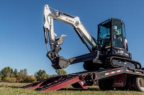 Operator unloads an R-Series E35 compact excavator off of a trailer.