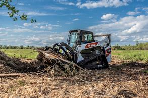 Bobcat compact track loader removing tree roots and brush