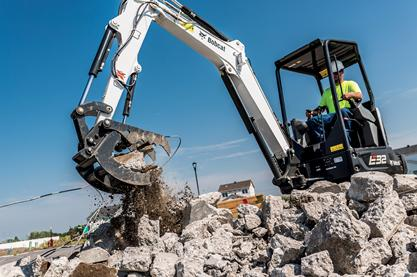 An R-Series E32 excavator moves demolished concrete on a jobsite.