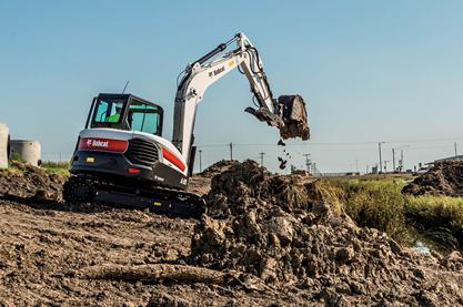 A Bobcat E85 compact excavator lifts a full bucket of dirt at a jobsite.