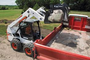 n operator uses an S630 skid-steer loader and a grapple attachment to load rocks into a truck bed.
