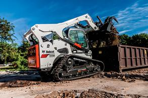 T870 compact track loader dumping a large load of debris into a waste container.