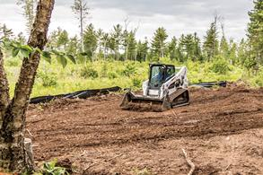 A Bobcat compact track loader moves dirt with a bucket.