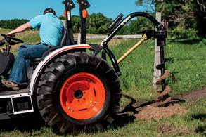 Bobcat compact tractor digs posthole with auger.