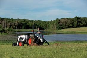 Bobcat compact tractor performs tasks on an acreage.
