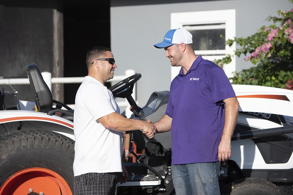 Bobcat Dealer Shakes Hand With Customer In Front Of Compact Tractor