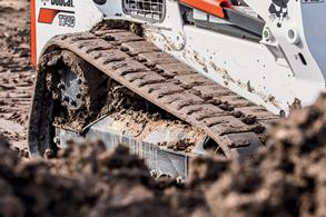 The tracks of a Bobcat T740 compact track loader move through mud.