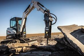 A Bobcat E35 compact excavator paired with a hydraulic breaker demolishes concrete.