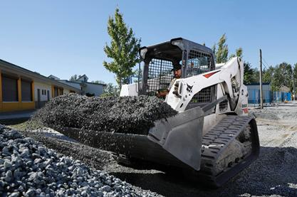 A Bobcat T650 compact track loader moves gravel on a construction jobsite.