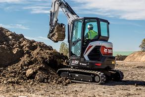 Bobcat compact excavator lifts dirt with bucket attachment.