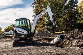 Operator using an R-Series E35 compact excavator to lift a pipe.
