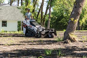 Man Grades Yard Using Soil Conditioner Attachment On Bobcat Mini Track Loader