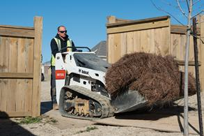 Man Carries Mulch Through Gate With Mini Track Loader And Bucket Attachment