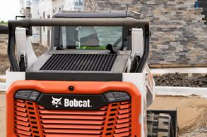 Man Smoothing Sand Using a Bobcat Compact Loader