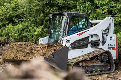 A T770 compact track loader uses a bucket to move dirt and mulch.