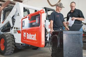 A service team inspects a Bobcat S650 skid-steer loader.