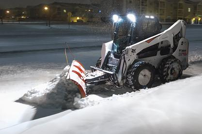 Bobcat S740 skid-steer loader with headlights and sidelights on plows snow from an apartment complex sidewalk at night.