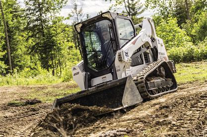 A Bobcat T595 compact track loader moves dirt with a bucket.