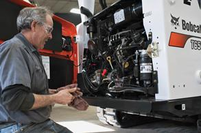 Bobcat mechanic servicing Tier 4 engine.