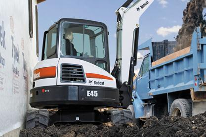 A Bobcat E45 compact excavator loads dirt in a confined space.