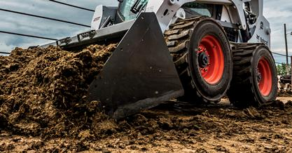 An S650 skid-steer loader with twin-flex solid tires uses a breaker to break up rock.