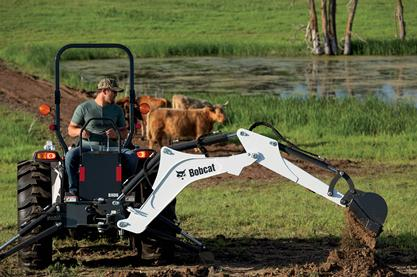 Operator digging with a compact tractor and backhoe tractor implement