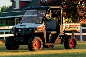 Bobcat UV34 Utility Vehicle Parked On An Acreage Lawn During Sunset