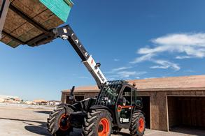 Bobcat VersaHANDLER telescopic tool carrier lifts plywood to the second level of a construction jobsite.