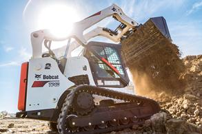 Bobcat T740 compact track loader dumps dirt with bucket.