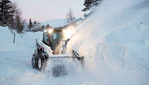Bobcat Skid-Steer Loader With Snowblower Attachment Blowing Snow.