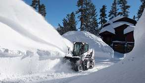 Bobcat Skid-Steer Loader Clears Tall Snow Piles With Snowblower Attachment