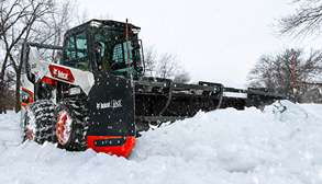 Bobcat Skid-Steer Loader With Chains On Tires Removes Snow With Snow Pusher Pro Attachment