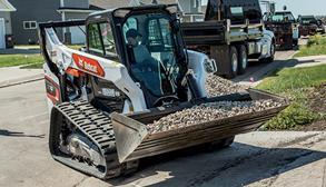 Bobcat R-Series Compact Track Loader With Bucket Attachment Moving Rocks Across Driveway