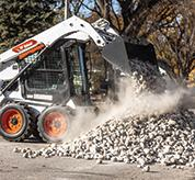 Operator Using Bobcat S450 Skid-Steer Loader With Bucket Attachment To Dump Rocks Onto Pile