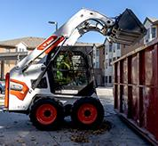 Operator Using Bobcat Skid-Steer Loader With Bucket Attachment To Dump Debris Into Dumpster