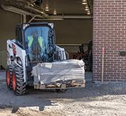 Operator Using Bobcat S450 Skid-Steer Loader With Pallet Fork Attachment To Move Material