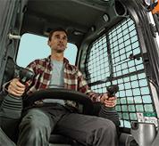 Operator Sitting In The Cab Of Bobcat S510 Skid-Steer Loader