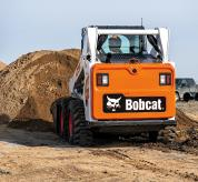 Operator Using Bobcat S590 Skid-Steer Loader With Bucket Attachment To Dig Dirt From Pile