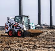 Operator Using Bobcat S590 Skid-Steer Loader With Bucket Attachment To Move Dirt On Construction Site